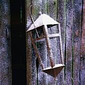 Lantern hanging on wooden wall