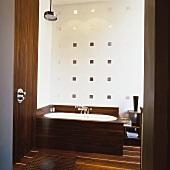 Blick ins Badezimmer mit holzverkleideter Dusche und Badewanne