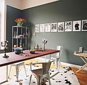 Designeresstisch mit Tolix Stühlen vor einer grünen Wand mit Fotoserie