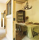 Esszimmer mit Korbstühlen und antikem Eckregal in einem umgebauten Stall