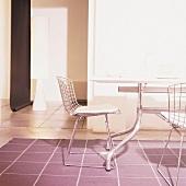 Metalltisch mit Wireframe Stühlen auf einem Teppich in Altrosa