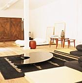 Verchromter Designercouchtisch und Futon in einem Wohnraum mit Stütz- und Deckenbalken