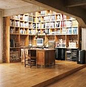Antiker Schreibtisch und Eckregal im Arbeitszimmer eines Betonbaus mit Backsteinwänden