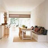 Esstisch und Holzbank in einem Esszimmer mit weißem Dielenboden und Fensterfront