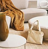 Detail einer modernen Sitzecke mit einer Handtasche und einem Beistelltisch im Vordergrund