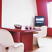 Ein roter Esstisch mit weissen Panton Stühlen in einer Zimmerecke mit leicht schräger Wand