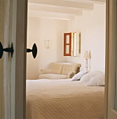 Blick in ein Schlafraum mit kleinem Fenster und sichtbaren Deckenbalken