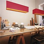 Der abgenutzte Holzschreibtisch erfährt durch die aufgelegte Glasplatte sowie Deko und moderne Deckenleuchten aufregende Akzente