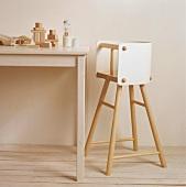 Ein schlichter Holztisch mit Bauklötzen und ein Hochstuhl