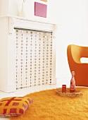 Die modernen Wohnzimmermöbel in knalligem Orange bilden einen effektvollen Kontrast zum umfunktionierten klassischen Kamin