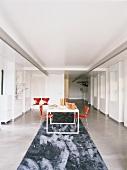Der weisse Designertisch mit den roten Stühlen stehen auf einem breiten Läufer, der die Schlauchform des Lofts unterschtreicht