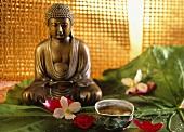A bowl of pu-erh tea, flowers and Buddha figure