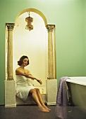 Eine Frau sitzt in der Nische eines orientalischen Badezimmers mit Säulen und Rundbogen
