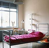 Ein schlichtes Metallbett in einem hellen Schlafzimmer mit kleiner Arbeitsecke