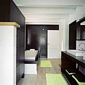 Ein puristisches Designerbadezimmer mit dunklen Holzoberflächen