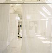 Indirekter Blick in einen Wohnraum durch halbtransparente Stoffbahnen