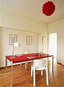 Der Tisch und die Deckenleuchte in sattem Rot durchbrechen das strenge Weiss des modern gestalteten Raumes