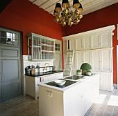 Die Küche mit Steinboden und roten Wänden versprüht modern-elegantes Landhausflair
