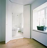 Blick durch eine einfache Flügeltür in ein weisses Badezimmer