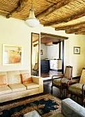 Elegante Antikmöbel im Wohnzimmer eines Landhauses mit traditioneller Holzbalkendecke