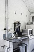 Eine zweckmäßige Küchenzeile mit Spülbecken und Elektrogeräten vor einer weissen Backsteinwand