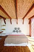 Eine ausgefallene Holzbalkendecke ist der Blickfang des spartanisch eingerichteten Schlafzimmers