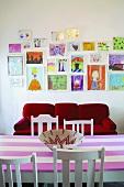 Vor der Wand mit Kinderzeichnungen stehen ein rotes Sofa und ein rosa gestreifter Esstisch