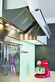 Eine rote Küchenmaschine in einer modernen Edelstahlküche