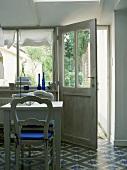 Ein Esszimmer mit gemustertem Fliesenboden und ländlich-romantischem Essplatz in Blau und Weiss