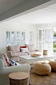 Naturmaterialien und viel Weiss in einer gemütlichen Sitzecke mit Terrassenzugang