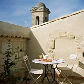 Eine kleine Sitzecke mit Bistrotisch auf der Dachterrasse