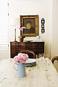 Blick über einen Tisch im Shabby Chic zu einer antiken Kommode mit Gemälde im barocken Goldrahmen