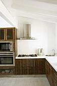 Eine interessante Mischung aus rustikalen Holzfronten und modernen Einbaugeräten in der Küche mit Dachschräge
