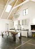 Ein antiker Holztisch auf Rollen vor einer weissen Holzküchenzeile in einer großzügigen Küche mit offenem Dachraum