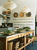 Kräuterschalen auf einem alten Küchentisch aus Holz mit Edelstahloberfläche