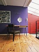 Ein schlichter Arbeitsplatz im hellen Dachgeschosszimmer mit Oberlicht und lebendigem Rot-Violett Kontrast