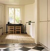 Der alte Holz- und Fließenfußboden verleiht der puristischen Designerküche einen besonderen Charme
