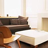 Ausschnitt eines Wohnraums mit großem Polsterhocker und Sofa neben einem Eames Chair