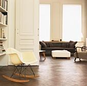 Die Schaukelstuhlversion des Plastic Armchair von Eames im eleganten Wohnzimmer mit Parkettfußboden und geöffneter Flügeltür