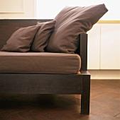 Detail eines eleganten Sofas mit Holzgestell und braunen Polsterkissen