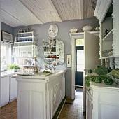 Ein Kronleuchter, ein eleganter Spiegel und dekorative Zierleisten an den Küchenmöbeln machen die verspielte Romantik der Küche aus