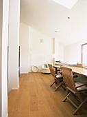 Zwei Holzklappstühle an einem Tisch im ausgebauten Dachgeschoss mit Oberlicht und Parkettfussboden