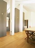 Ein einfacher Holztisch und zwei Stühle im ausgebauten Dachraum mit verputzten Stützpfeilern und Deckenbalken