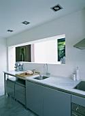 Eine schlichte Küchentheke im Aktenschrankstil vor einer L-förmigen Wandöffnung