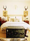 Ein antiker Überseekoffer vor einem gemachten Bett im rustikal dekorierten Schlafzimmer
