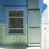 Eine traditionell orientalische Holztür neben einer Fensteröffnung mit eingebautem Metallgitter