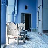 Weissgold gestrichene, niedrige Holzstühle und ein gedeckter Kaffeetisch im blauen Arkadengang eines orientalischen Wohnhauses