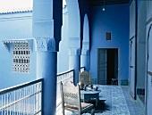 Ein Kaffeetisch mit Holzstühlen im Arkadengang eines blau gestrichenen, typisch orientalischen Wohnhauses