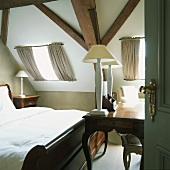 Elegante Antikmöbel in einem kleinen Dachgeschossschlafzimmer mit Holzbalkendecke