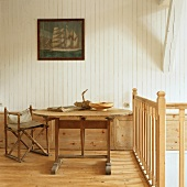 Ein alter Klappstuhl neben einem rustikalen Holztisch im ländlichen Ambiente eines Bauernhauses
